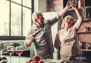 Older Couple With Nice Teeth Dancing While Preparing Dinner