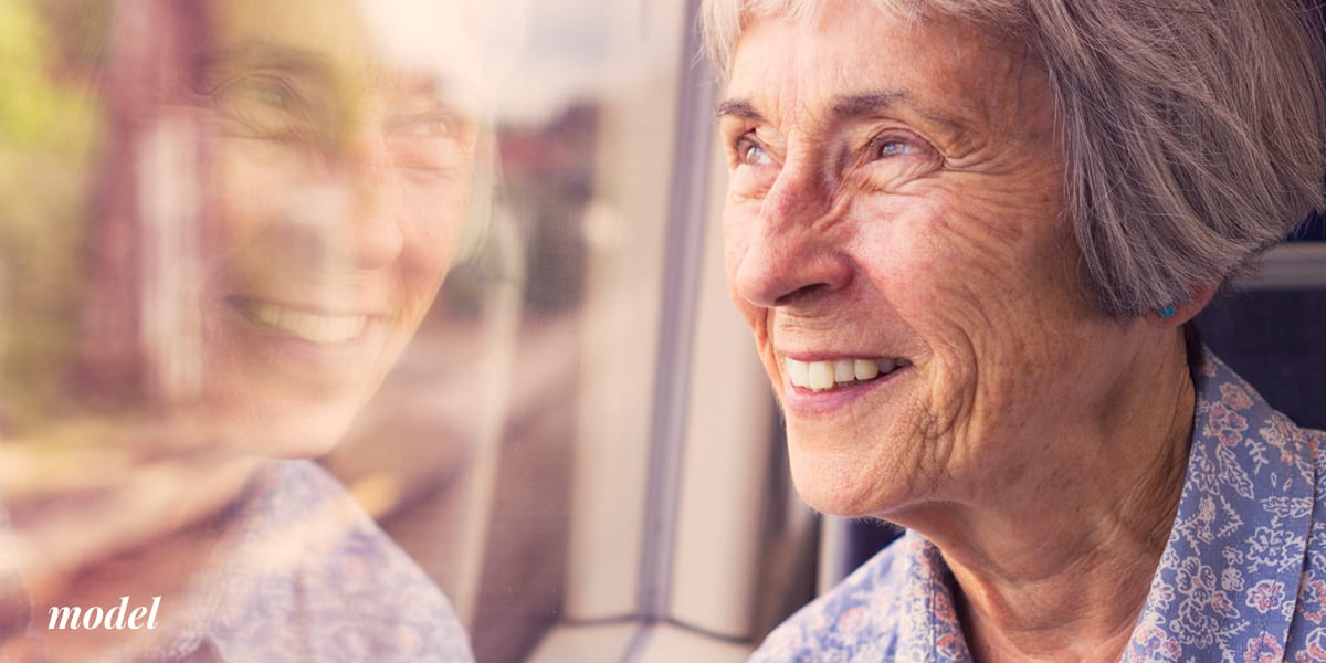 Older Female Considering Dental Implants Looking Out Window